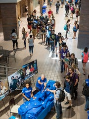 MTSU senior Katia Hope and Dean Ken Paulson of the College of Media and Entertainment hand out T-shirts in the lobby of the Bragg Building Wednesday during the college's celebration of its recent name change.