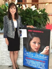 Sally Pacholok stands by a poster of the movie about her crusade to spread vitamin B12 deficiency awareness.