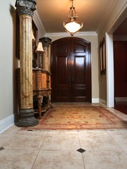 The formal entry features ornate columns and marble flooring.
