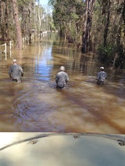 Louisiana National Guardsmen walk infront of a high-water