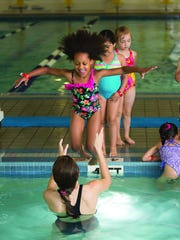 Ife Adejuwon of Belle Mead learns to confidently enter the water under the care of a YMCA instructor.