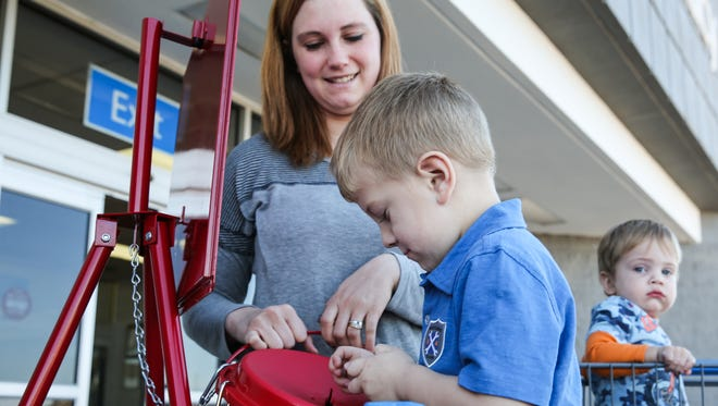 Reba Walston watches as her son Jakob, 4, drops money into a kettle during the Salvation Army Red Kettle Campaign on Wednesday outside a San Angelo Walmart.