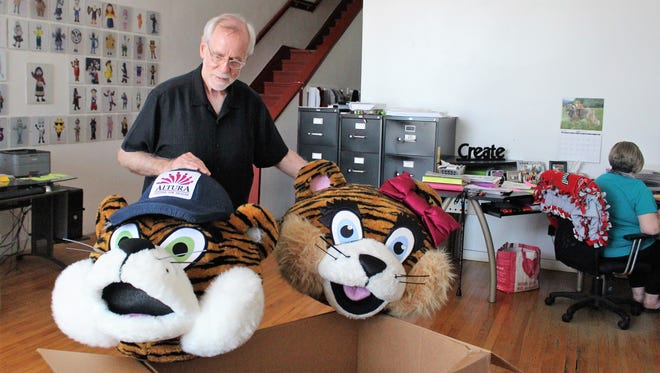 Dan Giles stands next to a box of old mascot heads, slated for cleaning, in the first floor of ProMo Costumes on West Center Street.