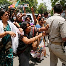 A woman pushes aside a policeman blocking the path during a protest against the gang rape of two teenage girls, in Allahabad, India, on May 31.