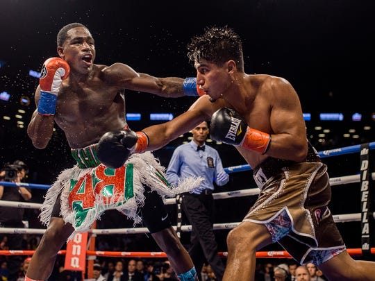 Adrien Broner, left, hits Mikey Garcia during a boxing bout Saturday, July 29, 2017, in New York. (AP Photo/Andres Kudacki)