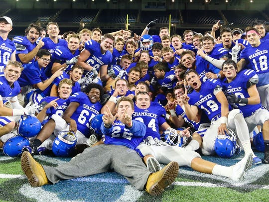 Catholic Central players celebrate at Ford Field after