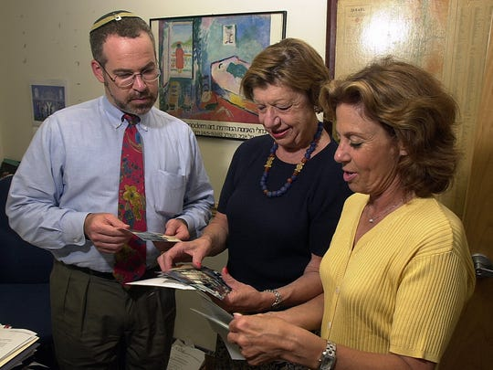 Lillian Adler (center) is shown here in an Aug. 9, 2001, file photo with Jonathan Feldstein and Barbara Wiener as they looked over photographs from their humanitarian trip to Cuba.