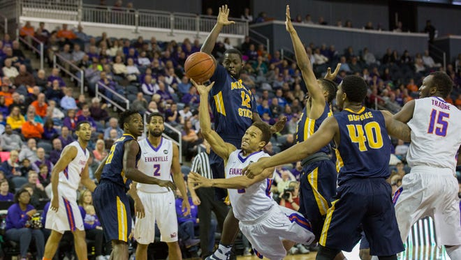 University of Evansville's Jaylon Brown gets fouled as Murray State's Gee McGhee (12) and Bryce Jones (32) jump up trying to block his shot during Saturday afternoon's game at the Ford Center.