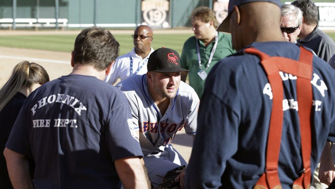Scottsdale Scorpions outfielder Tim Tebow waits 13 minutes for EMTs to respond to a fan who passed-out following his debut against the Glendale Desert Dogs on Tuesday, Oct. 11, 2016 during the Arizona Fall League in Glendale.