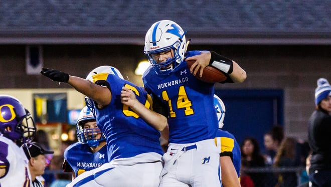 Mukwonago quarterback Cory Broncatti (14) celebrates a touchdown during the game at home against Oconomowoc on Friday, Sept. 8, 2017.