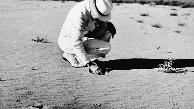 Rexford G. Tugwell, rural resettlement administrator and member of the U.S. president's drought commission, scoops a handful of loose sand that covers what was once a prosperous farm near Dalhart, Texas, Aug. 20, 1936, during the Dust Bowl.