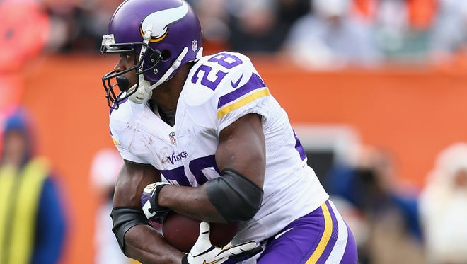 Adrian Peterson of the Minnesota Vikings runs with the ball against the Cincinnati Bengals in a 2013 game.