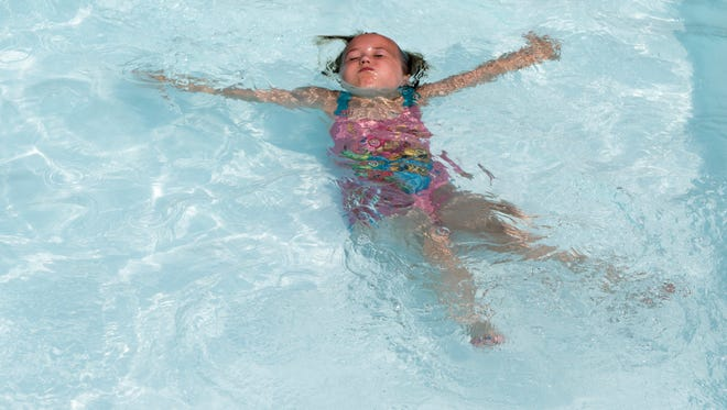 """Emmalin, 7, makes what she calls a """"water angel"""" in the shallow end of a pool at Camp Quality, a summer camp for kids with cancer and their siblings, at King's Camp in Mer Rouge, Thursday, July 27, 2017."""