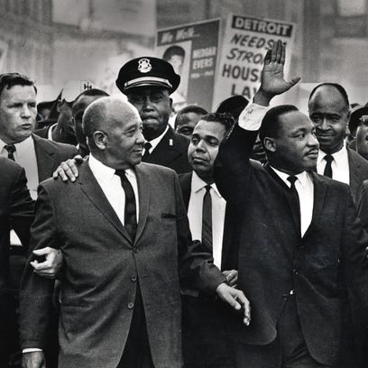 The Rev. Martin Luther King Jr. waves to onlookers