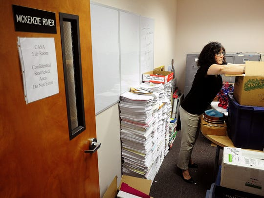 Lené Garrett, executive director of CASA, sorts through items as they move out of the Department of Human Services building Friday, May 29, in Salem.