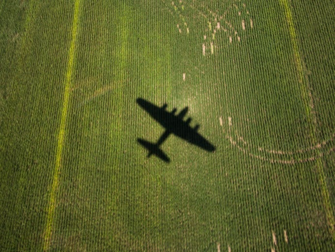 """The World War II B-17 bomber, """"Sentimental Journey,"""" casts a shadow as it flies over fields outside of Culpeper, Va. on Tuesday, Aug. 26, 2014. The plane will be available for cockpit tours and flights at Culpeper Regional Airport. (AP Photo/The Free Lance-Star, Scott Julian)"""