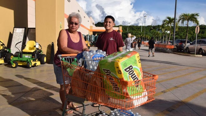 Gloria Guerrero shops with grandson Bryce Cruz, 14, for typhoon preparation supplies.