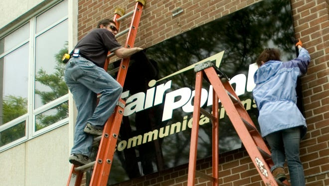 Workers install the new FairPoint Communications sign on a Burlington office building in May 2008. The company, which took over from Verizon, is being acquired by an Illinois-based company in a transaction worth $1.5 billion.