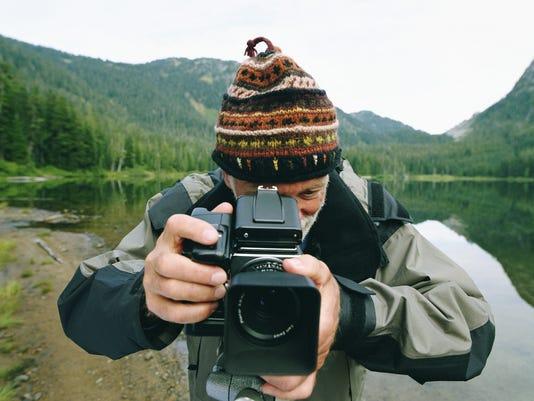 Senior man standing by lake, taking photo with medium format camera