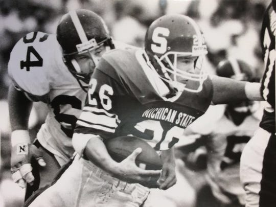 MSU tailback Blake Ezor runs with the ball, trying to escape Iowa's Dave Haight during the first half, Oct. 1, 1988