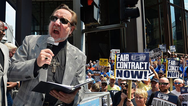 The Rev. Richard Freeman of the Interfaith Impact Network preaches to the crowd of steelworker and their supporters after a march from USW headquarters reached the USS headquarters on Grant Street,
