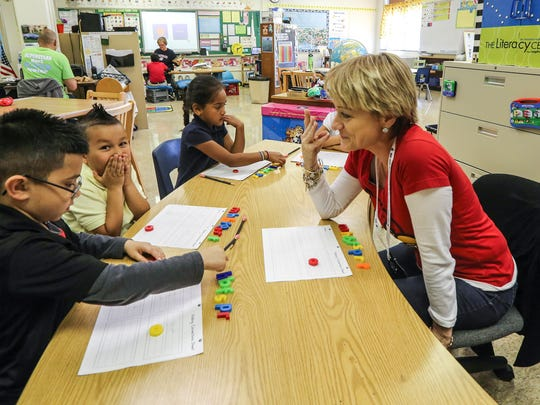 Patty Hannon, right, a Billingual Associate Instructor at Slaughter Elementary, works with Jeremy Torres, left, and other students as she teaches them English.  She is working on segmentation, deletion, vowels, and consonants. April 1, 2016