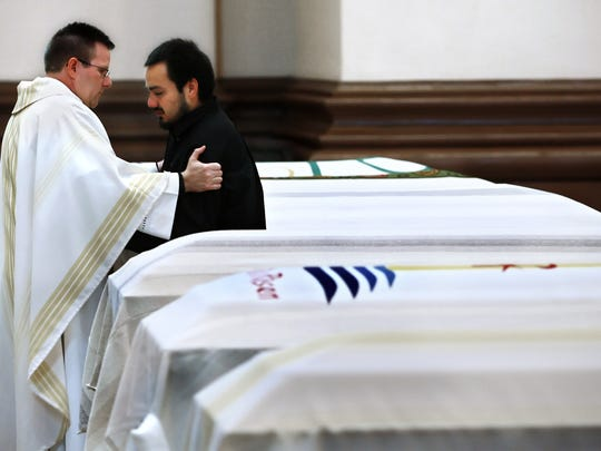 Mario Albarran, the only surviving son of Emma Valdez, one of six murdered, is consoled by Father Michael O'Mara of St. Mary's Catholic Church, as they stand in between the six caskets before Communion during the funeral held for the family members at SS Peter and Paul Cathedral.