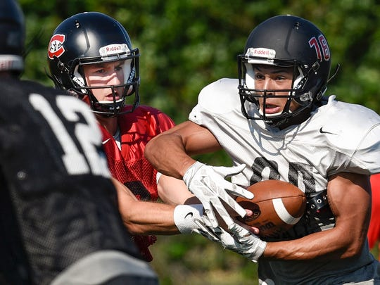 St. Cloud State Quarterback Nate Meyer, left, hands the ball off to John Pass during practice Monday, Aug. 22, 2016, at Husky Field.