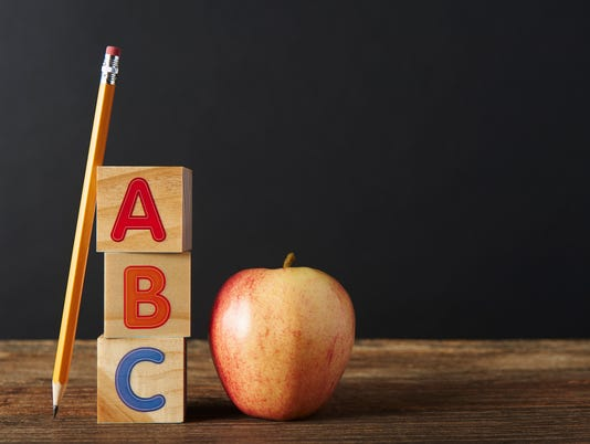 ABC Wooden spelling blocks, pencil and apple on wooden table
