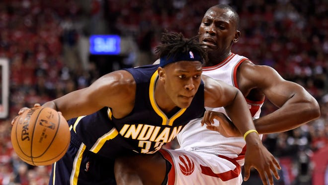 Toronto Raptors forward Bismack Biyombo, right, fouls Indiana Pacers forward Myles Turner during second half round one NBA playoff basketball action in Toronto on Sunday, May 1, 2016. (Frank Gunn/The Canadian Press via AP)