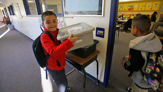 Carlos Palma, left, and Jesus Flores help carry boxes containing food Friday into Eldadiana Arzate's second-grade class at McCormick Elementary School in Farmington as part of the Breakfast Before the Bell program.