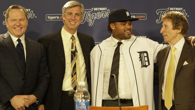 Prince Fielder, second from right, poses with for photos after putting on his new Tigers hat uniform shirt during his press conference as the Tigers newest player at Comerica Park in Detroit on Thursday, January 26, 2012. From left are Fielder's agent, Scott Boras, Tigers general manager Dave Dombrowski, Fielder and Tigers owner Mike Ilitch.