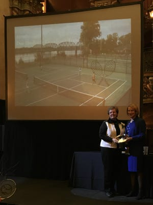 Henderson Tennis Club president Donna Spencer, left, accepts the award for Community Tennis Association of the Year at the United States Tennis Association of Kentucky's annual awards and honors dinner and reception on January 26 at the Louisville Palace.