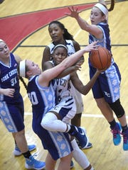 Lebanon Catholic's Neesha Pierre, center, tries to drive through the defense of Christian School of York's Bailey Stauffer during Tuesday's District 3 Class A semifinal at Cumberland Valley High School. Lebanon Catholic won, 59-36.