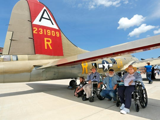 Robin Teegarden, from left, J. Scott Robbins, Chris Robbins and Helen Bournemouth Robbins sit in the shade beneath the tail of a B-17G Flying Fortress as they watch a p-51 Mustang taxis to a stop nearby Monday, August , 2016, at the Purdue University Airport. The planes were part of the Wings of Freedom Tour featuring vintage WWII planes. J. Scott Robbins was in the Army Air Force engineers in WWII.