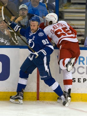 The Tampa Bay Lightning's Steven Stamkos, left, avoids a check from the Detroit Red Wings' Danny DeKeyser on March 22, 2016, in Tampa.