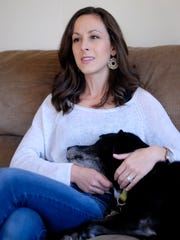 Ashley Troy sits with her dog Sunday, Nov. 15, at her home in Clyde Township.
