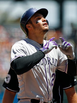 Colorado Rockies' Nolan Arenado reacts at the plate after hitting a two-run homer against the San Francisco Giants during the first inning of a baseball game, Sunday, June 28, 2015, in San Francisco.