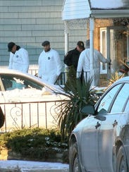 Investigators gather Jan. 1, 2018, outside a home in