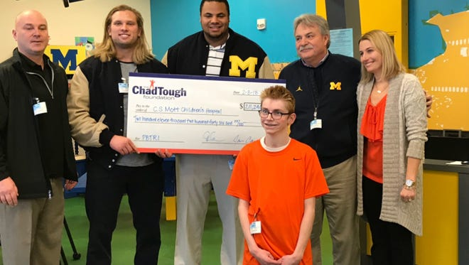 Michigan football players Chase Winovich and Grant Newsome, along with Tammi and Jason Carr of the ChadTough Foundation, presented Michigan Medicine's Pediatric Brain Tumor Research Initiative with a donation of $211,246 Thursday in Ann Arbor.