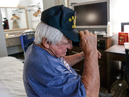 Jessie Alexander puts on a U.S. Army Veteran cap, while