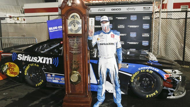 Martin Truex Jr. celebrates with his grandfather clock trophy after winning Wednesday's NASCAR Cup Series race in Martinsville, Va.