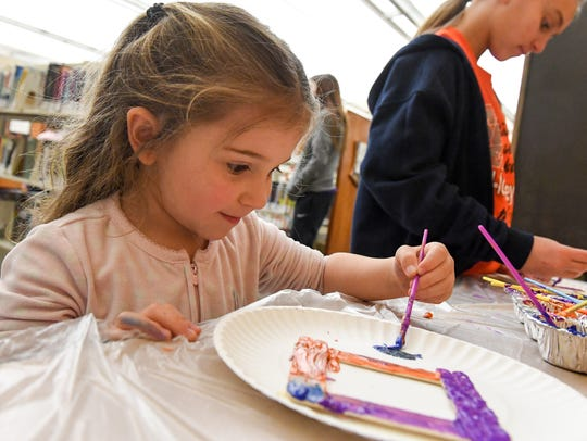 Lily Nowak, 3, smiles as she paints on Tuesday, March