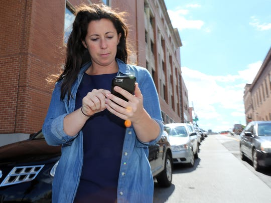 Jackie Rubbo, a Scarsdale resident who frequently uses the ride-sharing service Uber, uses the application on her mobile device on Main Street in Yonkers. She enjoys the convenience of the app and the ability to see and rate the driver.
