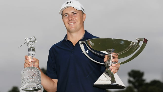 Jordan Spieth poses on the 18th green after winning both the TOUR Championship Sunday in Atlanta.