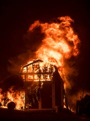 Flames from a wildfire consume a shed near Oroville, Calif., on Sunday, July 9, 2017. Evening winds drove the fire through several neighborhoods leveling homes in its path. (AP Photo/Noah Berger)