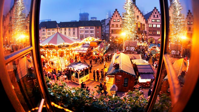 People enjoy a stroll at the traditional Christmas market in Frankfurt, Germany on Dec. 8, 2016.