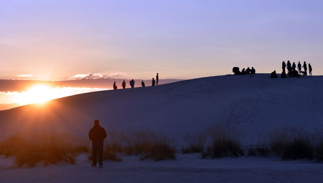 Visitors watch the sunrise from atop the White Sands National Monument dunes during the 26th annual White Sands Balloon Invitational in September.