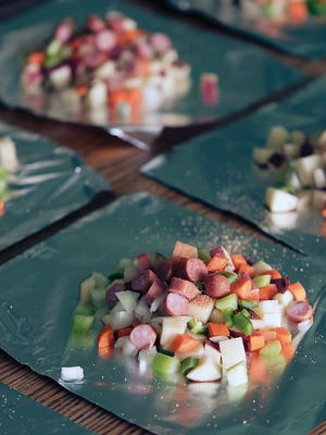 Vegetables and meats are chopped and put into foil wrapper for cooking in gas grill, oven, or campfire, (depending on fire regulations and conditions in your area).
