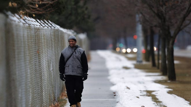 James Robertson, 56, of Detroit, walks along Crooks Rd. while walking to his job at Schain Mold & Engineering in Rochester Hills on Thursday January 29, 2015.